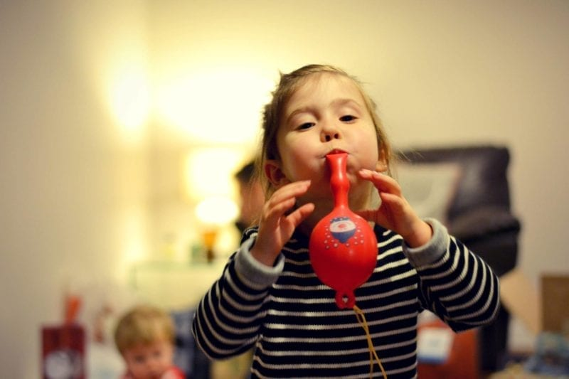 child blowing up a balloon